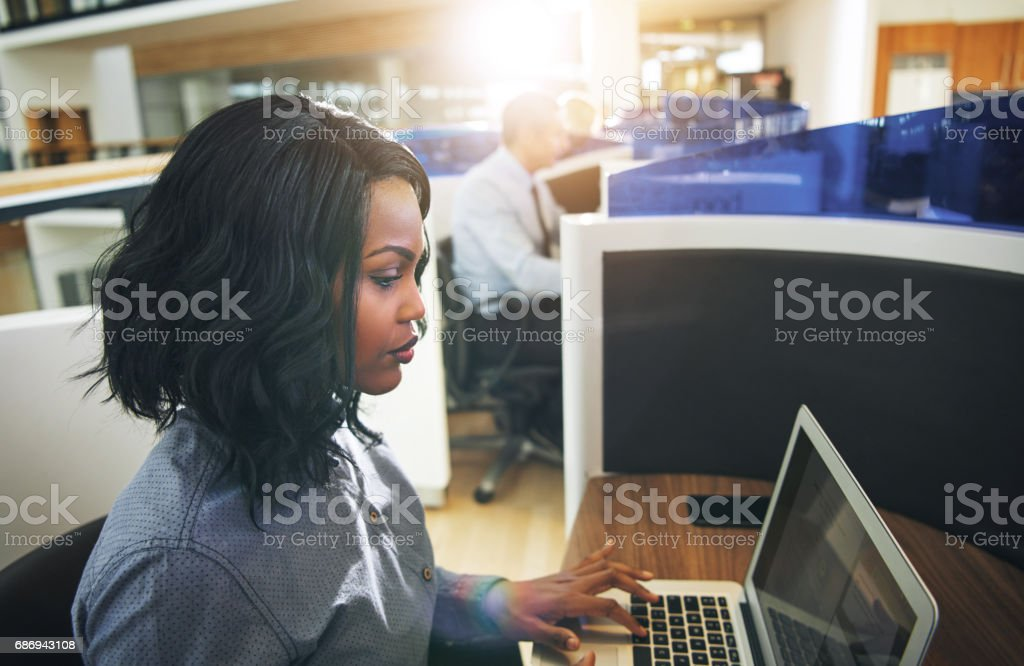 Young black woman typing laptop at workplace in office stock photo
