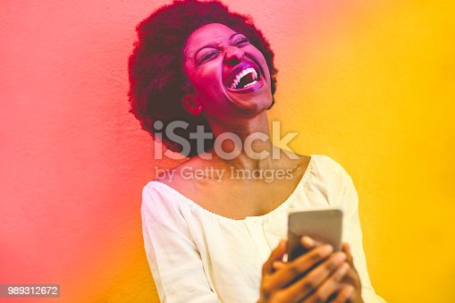 istock Young black woman using smart mobile phone - African girl laughing and smiling using web app on cellphone - Youth lifestyle and technology concept - Radial red and yellow filter editing 989312672