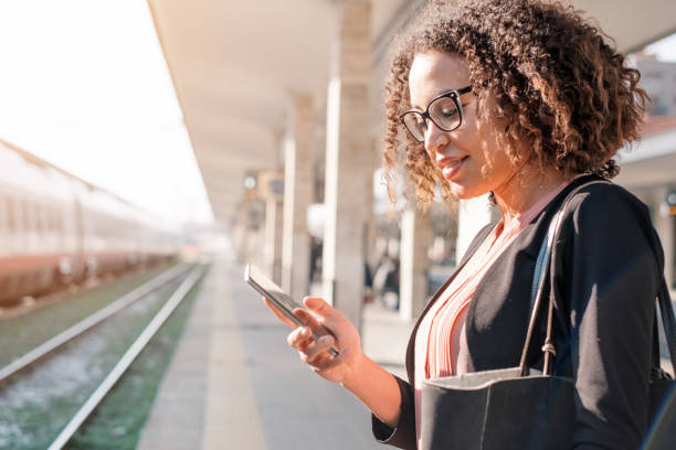 Young black woman waiting for the train Young black woman waiting for the train on station platform railroad station platform stock pictures, royalty-free photos & images