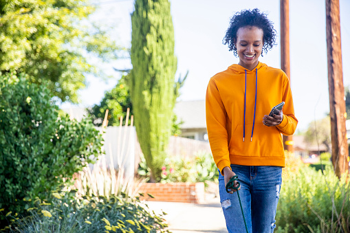 Young Black Woman Walking Dogs with Smartphone