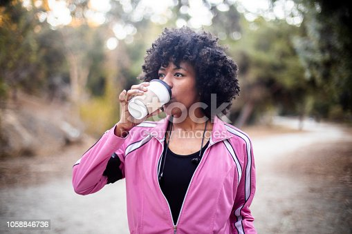 A young black woman walking with a cup of coffee