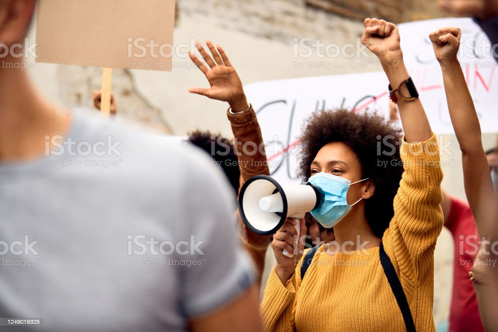Young black woman wearing protective face mask while shouting through megaphone on anti-racism solidarity protest. African American woman wearing protective face mask  while shouting through megaphone in solidarity with the movement. Activist Stock Photo
