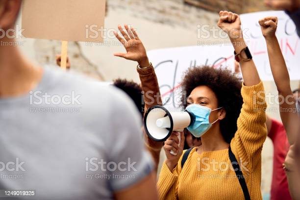 Young Black Woman Wearing Protective Face Mask While Shouting Through Megaphone On Antiracism Solidarity Protest Stock Photo - Download Image Now