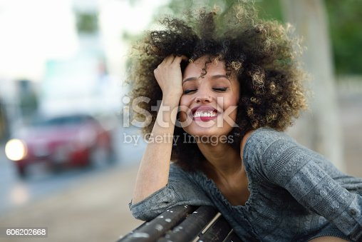 istock Young black woman with afro hairstyle smiling in urban backgroun 606202668
