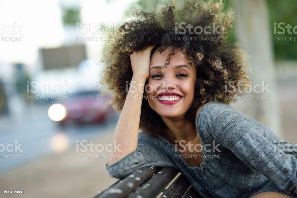 Jovem negro mulher com um penteado afro, sorrindo em meio urbano - foto de acervo