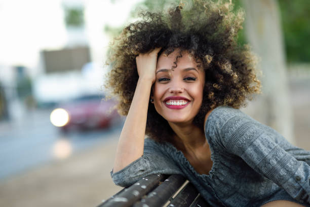 Young black woman with afro hairstyle smiling in urban background stock photo