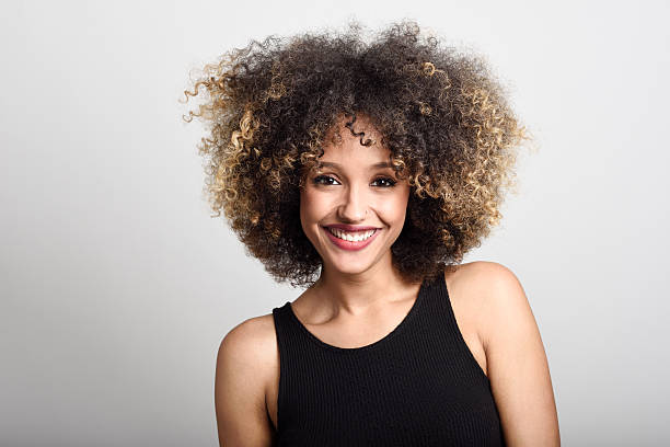 Young black woman with afro hairstyle smiling - foto de acervo