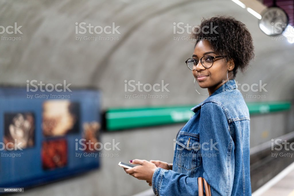 Young black woman with afro hairstyle using mobile in the subway - fotografia de stock