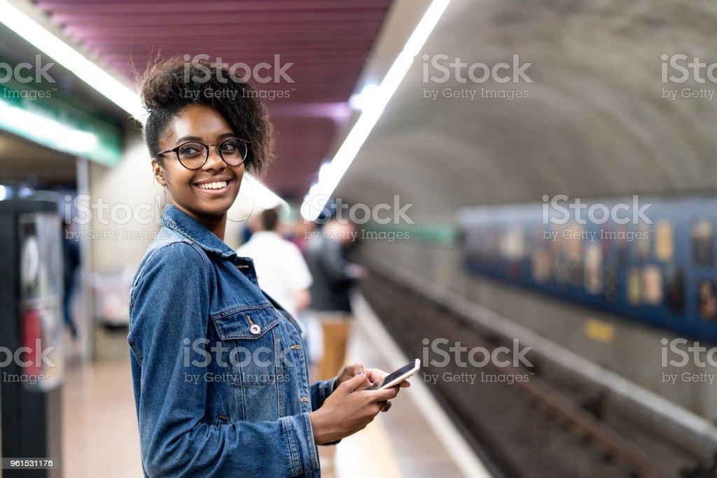 Joven negro con peinado afro con móvil en el metro - foto de stock