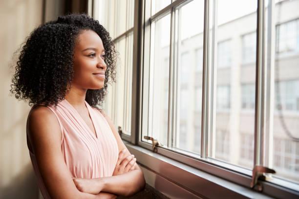 Junge schwarze Frau mit verschränkten Armen Blick aus Fenster – Foto