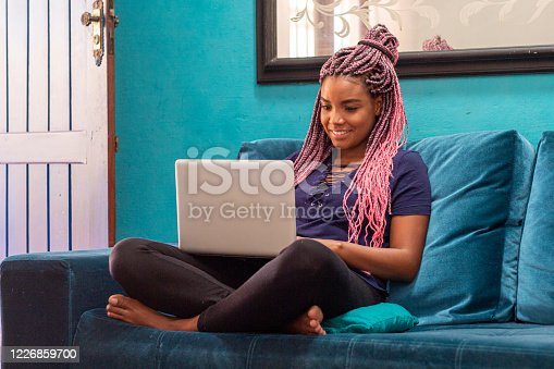 Young black woman with pigtails using notebook sitting on blue sofa in home room