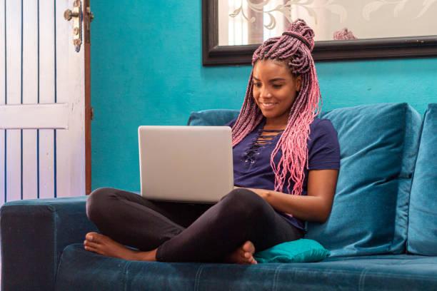 年輕的黑人婦女與辮子使用筆記本在家庭房間 - 年輕成年人 個照片及圖片檔