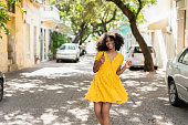 istock Young black woman with curly hair, in yellow dress and with styles, attitude, laughing, happy 1295901898