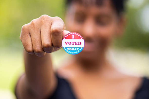 Young Black Woman with I Voted Sticker A young black woman holds an I Voted sticker civil rights stock pictures, royalty-free photos & images