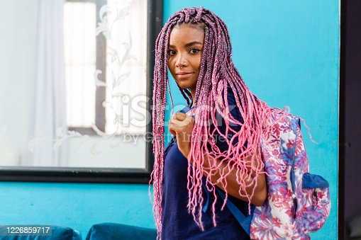 Young black woman with pigtails waving goodbye with colorful backpack leaving room with blue wall