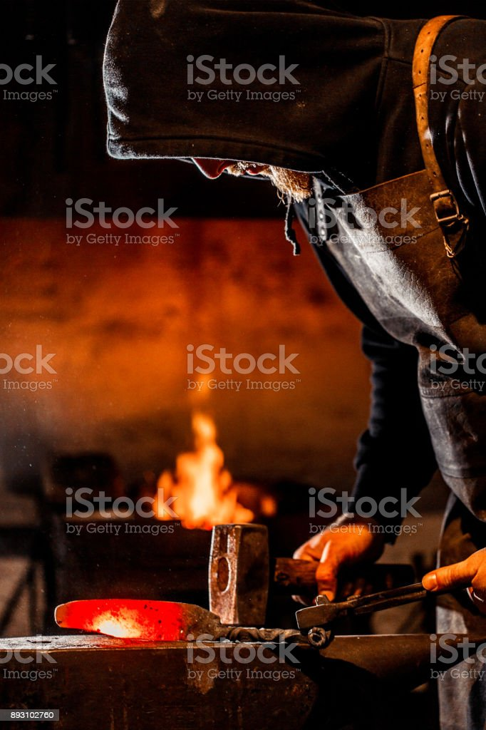 Young Blacksmith Shaping Glowing Knife Iron Blade On Anvil stock photo