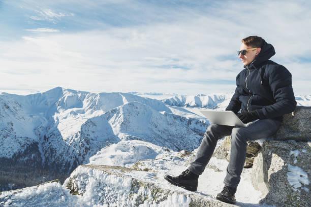 junge blogger oder freiberufler arbeiten auf einem laptop an der weltspitze. winter-landschaft in sonnigen tag. - reiseblogger stock-fotos und bilder