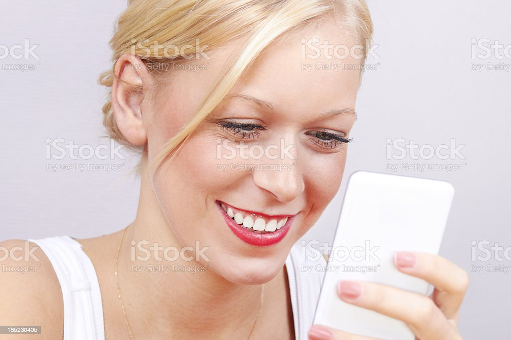 young blond adult woman holding white smartphone headshot royalty-free stock photo
