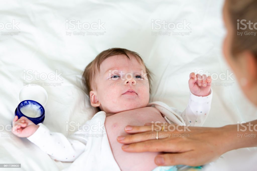 junge blonde schöne Mutter oder Arzt ist ihr Baby eincremen. – Foto