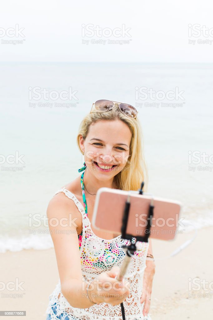 young, blond beautiful woman doing selfie photo with her smartphone on a great beach in thailand stock photo