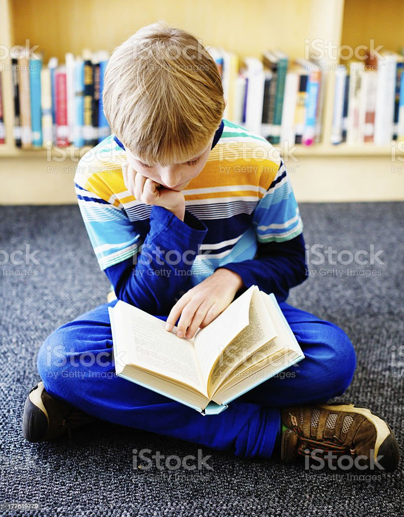 Young blond bookworm sitting on library floor absorbed in reading royalty-free stock photo