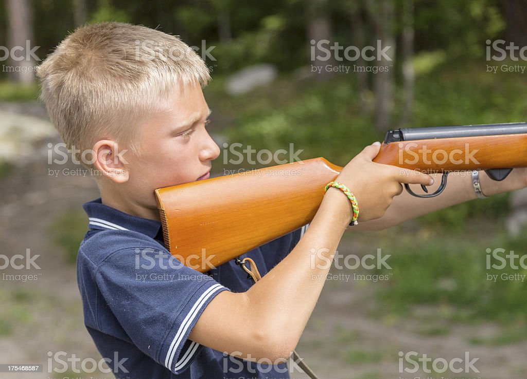 Young blond boy shooting with air gun stock photo