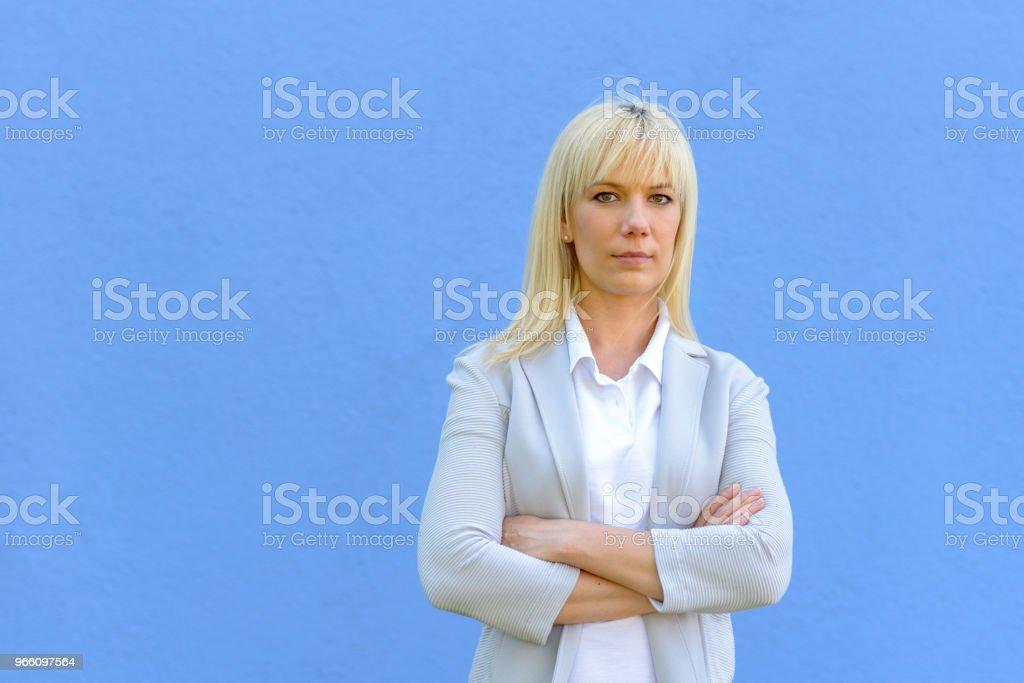 Ung blond affärskvinna med korslagda armar - Royaltyfri Affärskvinna Bildbanksbilder