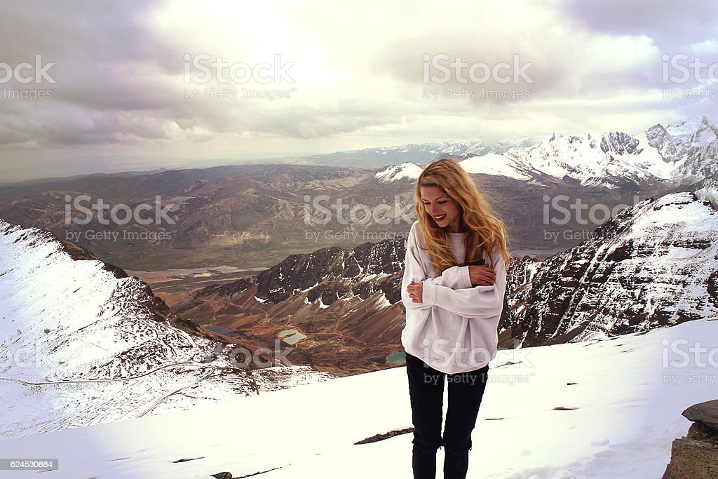 young blond caucasian smiling woman freezing in mountain, Bolivia stock photo