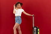 Young blond curly woman in a sundown hat with grey luggage bag is excited at sightseeing tour while standing infront of a red background. Concept of traveling