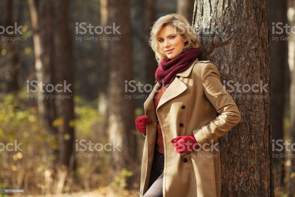 Young blond fashion woman in classic beige coat walking outdoor stock photo