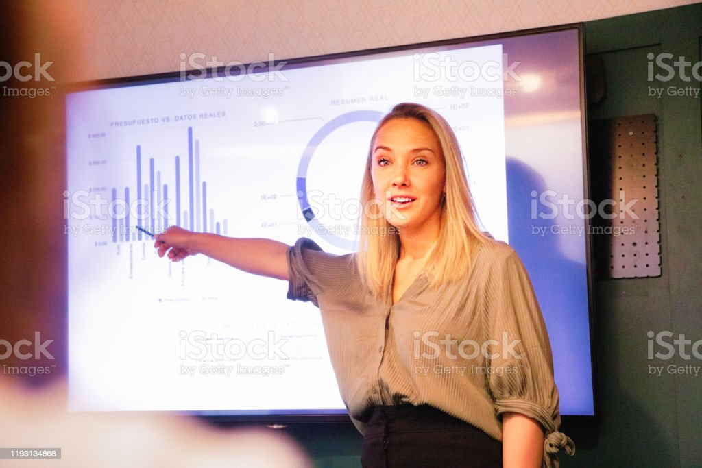 Young blond female manager explaining quarterly results on large led screen Young blond female manager explaining quarterly results on large led screen with a nice energy. Over the shoulder view suggesting she is addressing someone in particular. Administrator Stock Photo