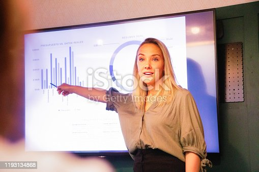 Young blond female manager explaining quarterly results on large led screen with a nice energy. Over the shoulder view suggesting she is addressing someone in particular.