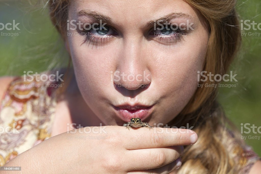 young blond girl gives green lake frog reptile fairytale kiss stock photo