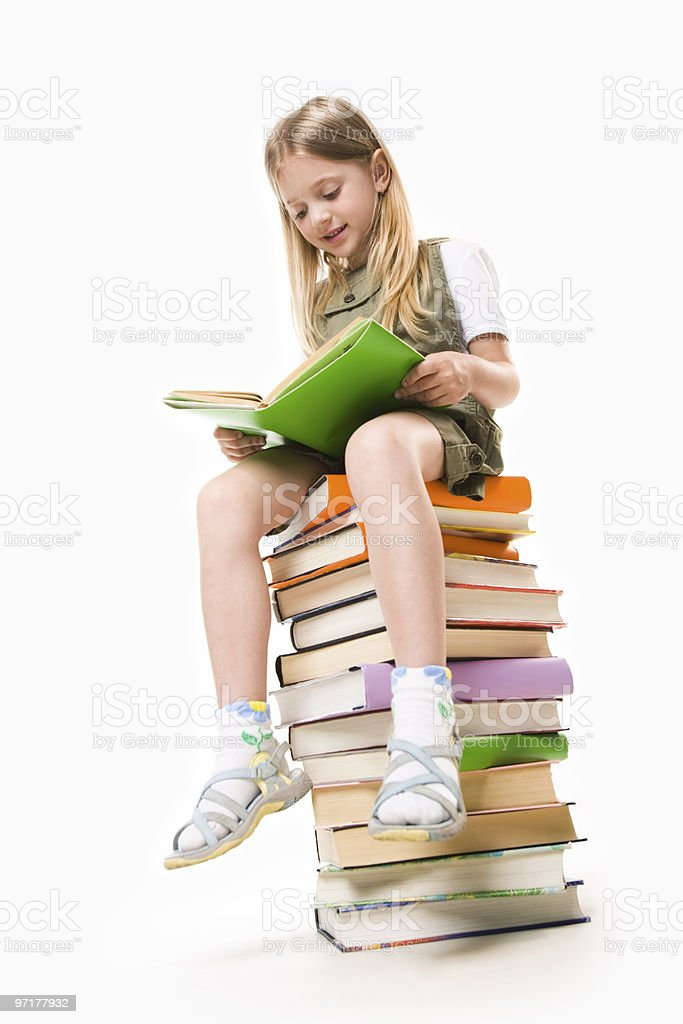 Young blond girl sitting on a tall stack of books reading royalty-free stock photo