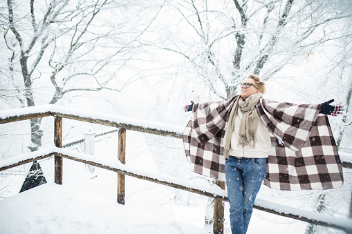 Young blond hair woman covering herself with blanket in the winter forest.