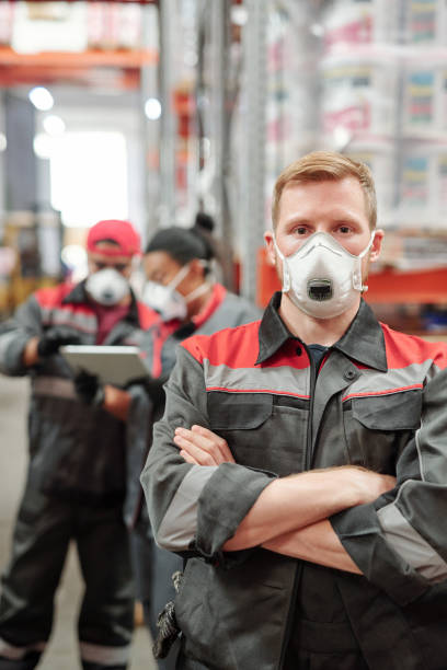 Young blond man in workwear and protective respirator crossing his arms by chest stock photo