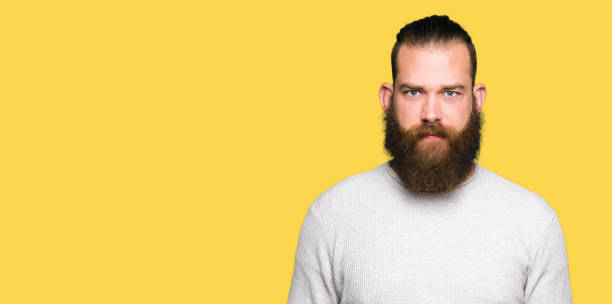 Young blond man wearing casual sweater skeptic and nervous, frowning upset because of problem. Negative person. Young blond man wearing casual sweater skeptic and nervous, frowning upset because of problem. Negative person. man bun stock pictures, royalty-free photos & images