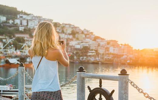 Young blond tourist woman making photo of sunset, Alanya, Turkey