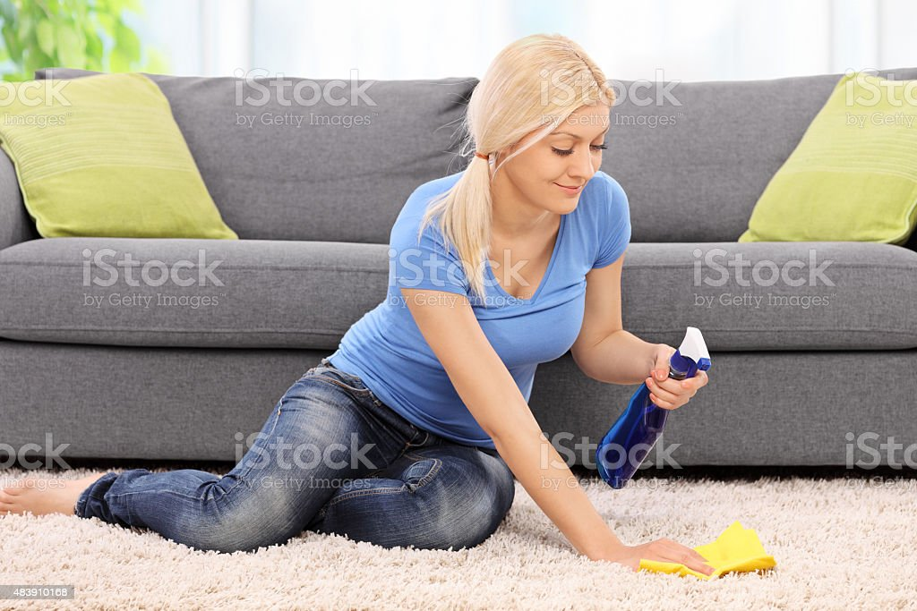 Young blond woman cleaning a carpet stock photo