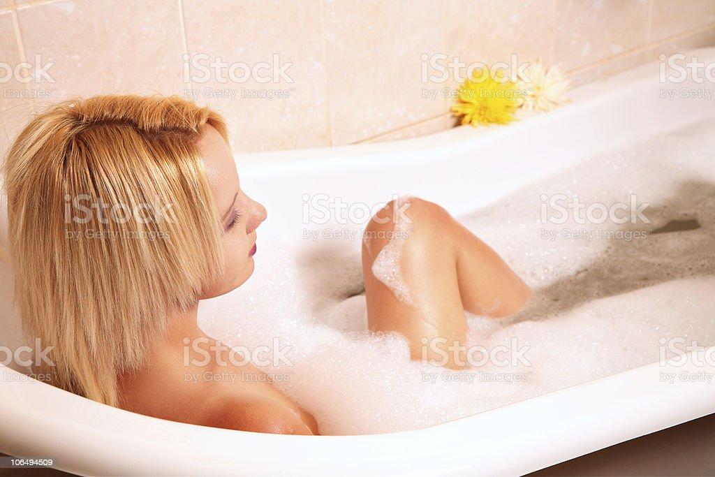 Young blond woman enjoying a foam bath royalty-free stock photo