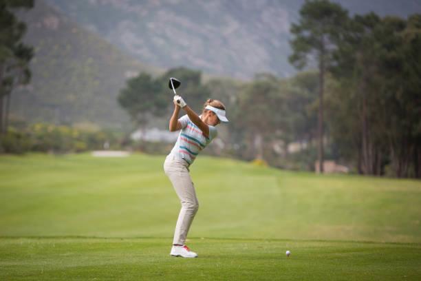 junge blonde frau, die den golf ball - schiebermütze stock-fotos und bilder