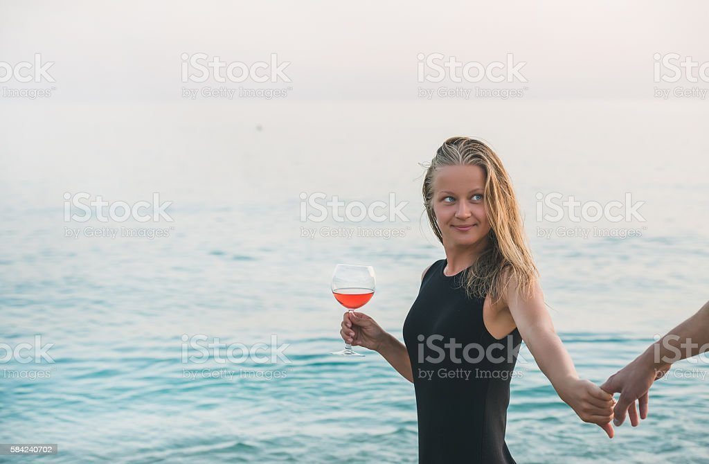 Young blond woman holding glass of rose wine and man stock photo