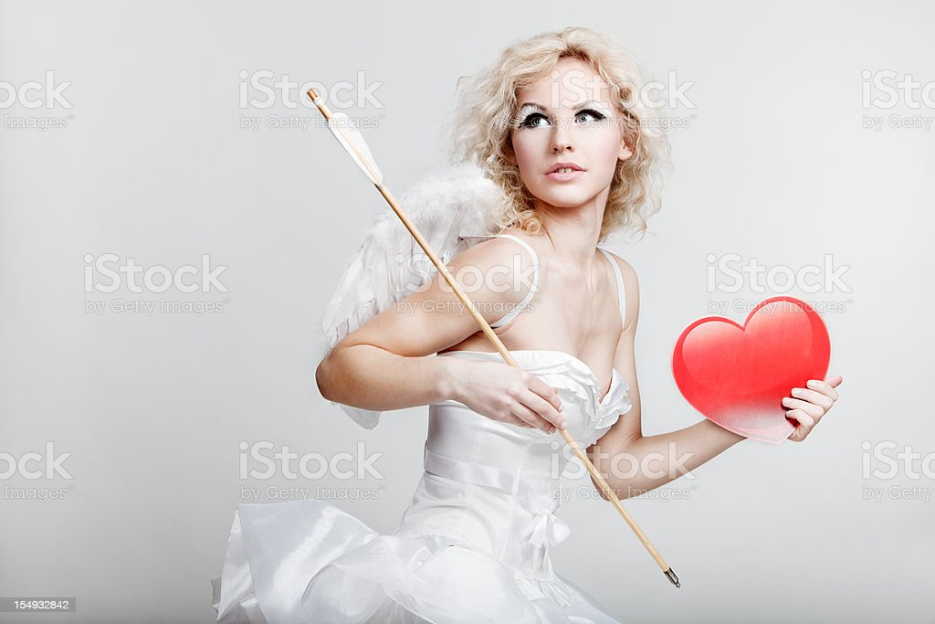 young blond woman in angel costume holding heart stock photo