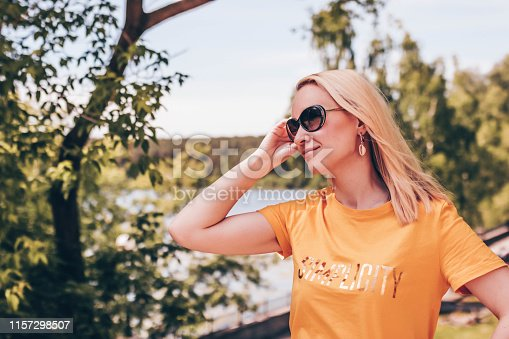 istock Young blond woman in sunglasses and yallow t-shirt posing on a sunny day outdoors. 1157298507