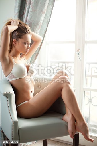 Beautyful young blond woman sitting in the chair next to the window and wearing white lingerie. Girl with both hands holding her hair. She is very sensual and attractive.