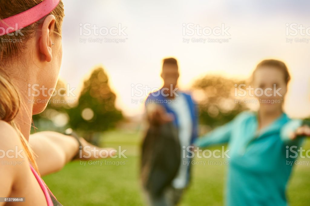 Young blond woman leading a yoga class at sunset in stock photo