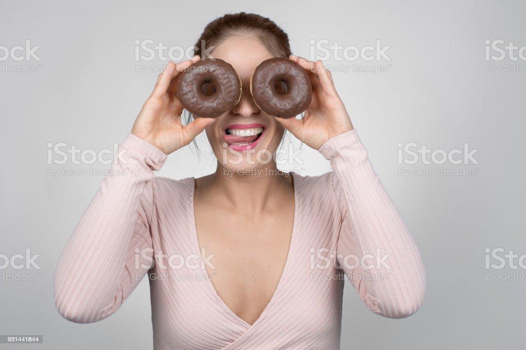 Junge, blonde Frau schaut durch zwei donuts – Foto