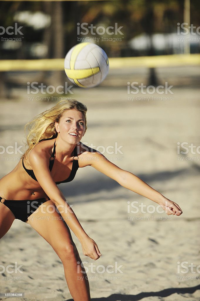 Young Blond Woman playing beach volleyball stock photo