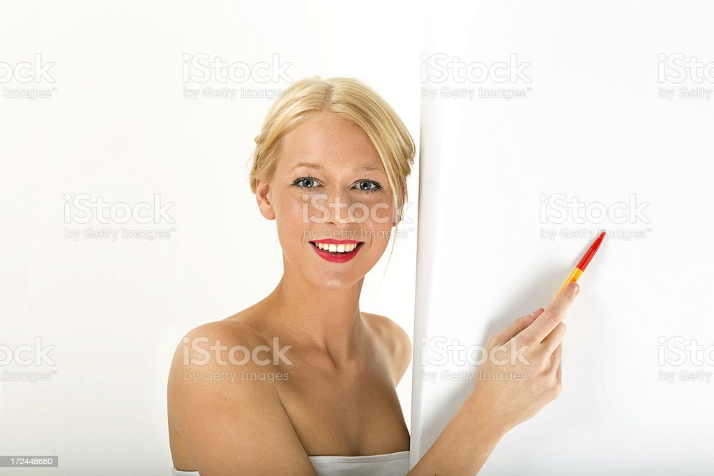 Young blond woman pointing to copy space with a pen stock photo