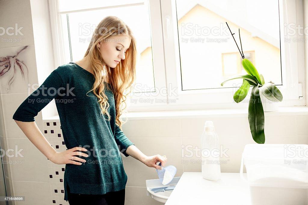 Loira jovem passando debaixo de lavar roupa em pó - foto de acervo